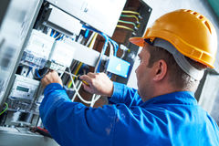 Electrician installing energy saving meter. Into switch box panel Stock Photo