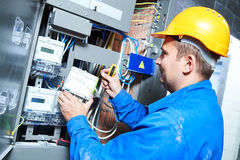 Electrician installing energy saving meter. Into switch box panel Royalty Free Stock Image