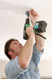 Electrician Installing Fan Box. An electrician using a drill to install a fan box in the ceiling.  Work is being performed to NEC code standards by a licensed Royalty Free Stock Photo