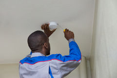 Electrician Installing Fire Sensor. Young Male Electrician Installing Fire Sensor On A Ceiling royalty free stock photo