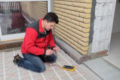 Electrician installing heating electrical cable on concrete floor. Man measure resistance of cable. Energy-saving technologies for home comfort royalty free stock images