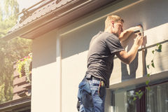 Electrician installing lamp on house facade stock photos