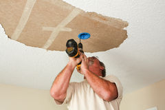 Electrician installing light fixture on ceiling. An electrician drills a hole into a ceiling to install an electric light fixture.  An area of acoustic ceiling Stock Images