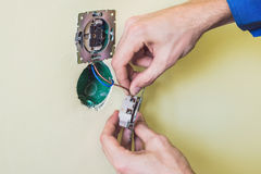 Electrician Installing Socket In New House. Electrician in the house Royalty Free Stock Image