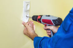 Electrician Installing Socket In New House. Electrician in the house Royalty Free Stock Images