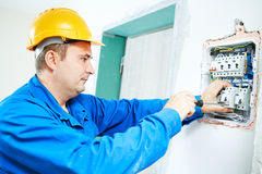 Electrician installing switching electric actuator in fuse box Stock Photos