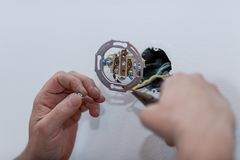 Electrician installing a wall-mounted AC power socket with a scr stock photography