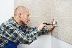 Electrician installing wall outlets stock photo