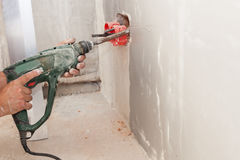 Electrician installing wall power socket, plastic electrical junction box with drill. Stock Images