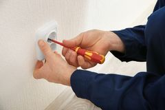 Electrician installing wall socket in new building. Closeup stock photos
