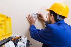 Electrician installing wall socket Royalty Free Stock Photos