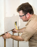Electrician Installing Wiring. In an insulated wall.  Focus on electrician Stock Images