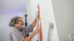 Electrician installing wiring in a wall Royalty Free Stock Photo