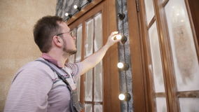 Electrician installs bulb in lighting system on decorative wall. Qualified worker man screws lamps in chain of inside light around two fake door in photo stock footage