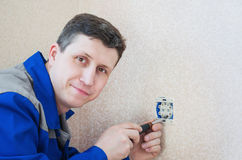 The electrician installs an electrical outlet in the apartment. Royalty Free Stock Photos