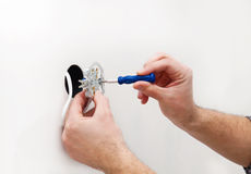 The electrician installs electrical outlet Stock Image