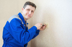 The electrician installs an electrical outlet Stock Photo