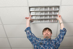 Electrician installs lighting to the ceiling. Electrician installs lighting to the ceiling in the office Royalty Free Stock Photo