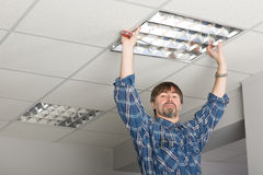 Electrician installs lighting to the ceiling. Electrician installs lighting to the ceiling in the office stock photography