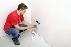 Electrician installs a new outlet indoors royalty free stock images