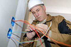 Electrician installs paired socket on wall Stock Photography