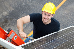 Electrician Installs Solar Panel. Young electrician on a ladder installing solar panels Stock Images