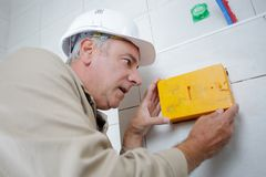 Electrician installs wiring box in new apartment. Man royalty free stock photo