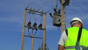 Electrician with laptop at the transformer. In summer day stock video footage