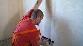 Electrician laying wiring cable lines inside of wall. Construction worker mounting electricity wires. Safety policy, technology, repair, interior design stock video
