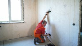 Electrician laying wiring cable lines inside of wall. Construction worker mounting electricity wires. Safety policy, technology, repair, interior design stock video footage