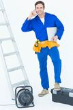 Electrician with leg on tool box using mobile phone Stock Image