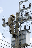 Electrician lineman at climbing work on electrical power pole. Stock Image