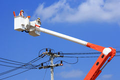 Electrician lineman  on  hydraulic platform. Electrician lineman repair of  electric power system on  hydraulic platform Royalty Free Stock Image