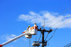 Electrician lineman repair of  electric power system. On  hydraulic platform Royalty Free Stock Photography