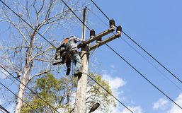 Electrician lineman repairing work on electric. Post power pole Stock Photos