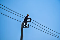 Electrician lineman repairing work on electric post power pole Stock Images