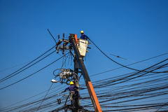 Electrician lineman repairing work on electric post power pole Royalty Free Stock Photo