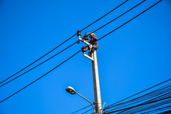 Electrician lineman repairing work on electric post power pole Stock Photos