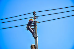 Electrician lineman repairing work on electric post power pole Royalty Free Stock Images