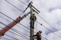 Electrician lineman repairman worker at climbing work on electric post power pole Stock Photography