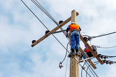 Electrician lineman repairman worker at climbing work on electric post power pole. Thai language same safty fist in English language Royalty Free Stock Photography