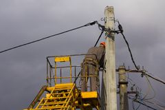 Work on electric post power pole Electrician lineman repairman worker at climbing Royalty Free Stock Photos