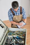 Electrician looking at fuse box. Holding Clipboard stock photography