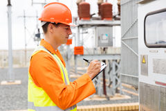 Electrician machine readings. Young electrician taking machine readings in substation Royalty Free Stock Images