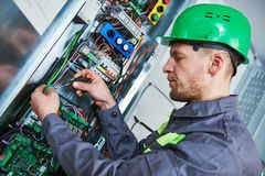 Electrician make maintenance in engine room of elevator. Elevator installation and maintenance. lift machinist electrician worker adjusting eelectronic control royalty free stock image