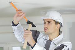 Electrician making hole on ceiling. Electrician making a hole on the ceiling Royalty Free Stock Photography