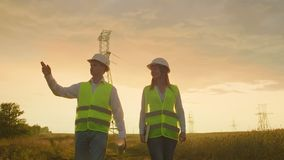 An electrician male and female in the fields near the power transmission line. He is an electrician who manages the. Process of erecting power lines. The stock footage