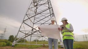An electrician male and female in the fields near the power transmission line. He is an electrician who manages the. Process of erecting power lines. The stock video footage
