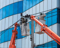 Electrician Man on Crane lifts. Electrical repairs on poles Stock Photography