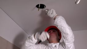 Electrician man with cutter tool removing insulation from wires in ceiling stock footage
